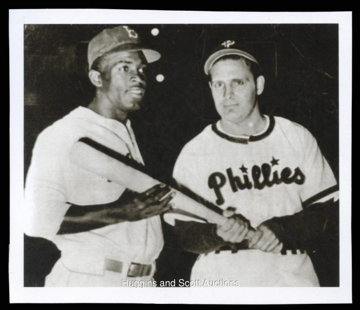 The pressure of integration: Chapman and Robinson jointly hold a baseball bat.  Image source: galleryhip.com