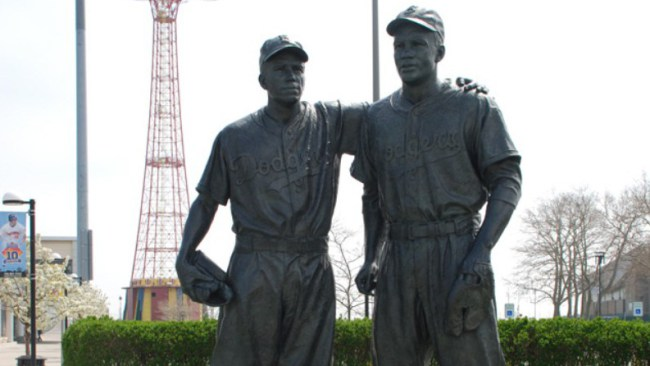 A statue of Jackie  Robinson with Pee  Wee  Reese putting his arm around him at Crosley Field stands in front of MCU Park at Coney Island in Brooklyn today as a symbol of courage and diversity in baseball.  Image source: thegrio.com